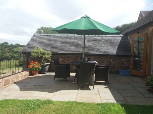 Outside garden area with table, chairs & sun umbrella